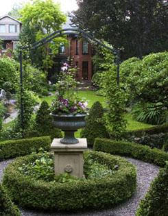 Dinnick Garden, green urn on a cream plinth