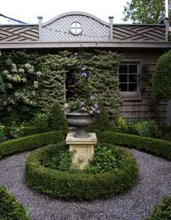 A formal parterre of boxwood with a circle of gravel around a handsome urn mounted on a plinth